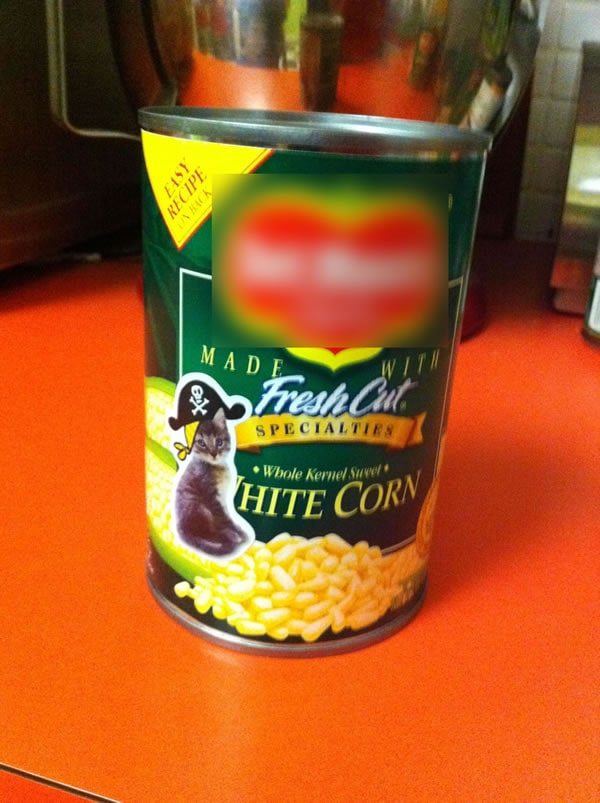 A can of corn with an image of a pirate cat on it.