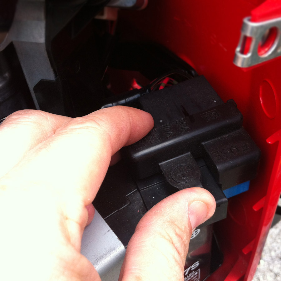 Popping off the Honda Ruckus fuse box cover.